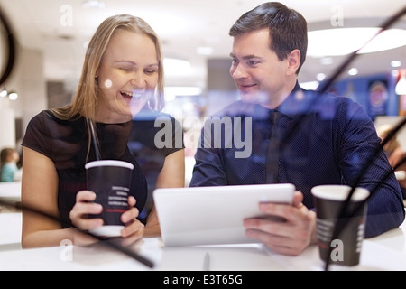 Woman laughs as man shows tablet - Stock Photo