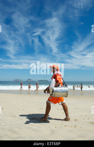 RIO DE JANEIRO, BRAZIL - MARCH 10, 2013: Brazilian beach vendor selling South American mate tea walks in uniform - Stock Photo
