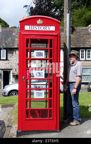 Tourist reading a poem on a  converted phone box in the Derbyshire Village of Tideswell - Stock Photo