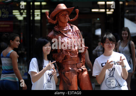 Vancouver, Canada. 28th June, 2014. Human statue Copper Cowgirl of Canada poses for a photo with two volunteers - Stock Photo