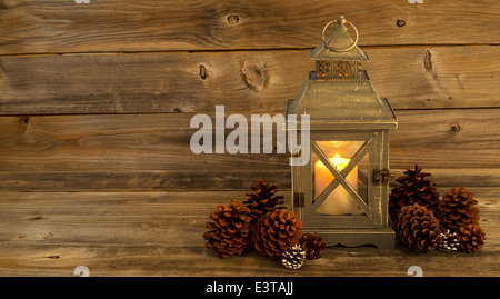 old Asian design lantern and white candle glowing brightly inside with natural pine cones decorations on rustic - Stock Photo
