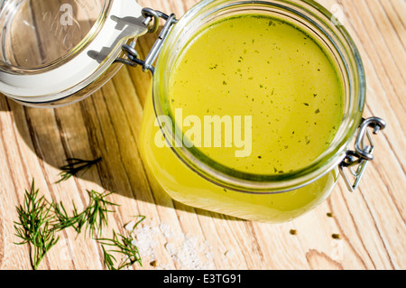 Canned broth, bouillon, clear soup in a glass jar - Stock Photo