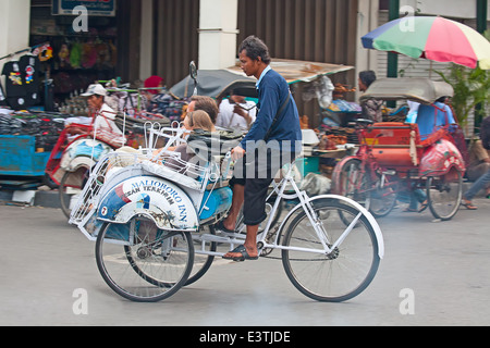 YOGYAKARTA - AUGUST 03: Traditional rikshaw transport on streets of Yogyakarta, Java, Indonesia on August 03, 2010. - Stock Photo