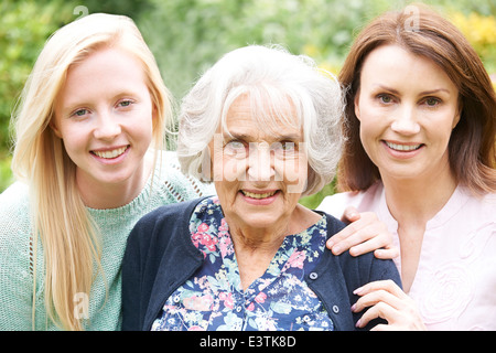 Portrait Of Grandmother, Daughter And Granddaughter In Garden - Stock Photo
