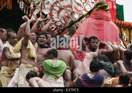 Puri, Orissa of India. 29th June, 2014. Hindu devotees carry an avatar of the god to the giant chariot during the - Stock Photo