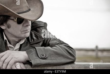 Portrait of a pensive, modern day cowboy, leaning against fencing. Colours removed but not quite black & white. - Stock Photo