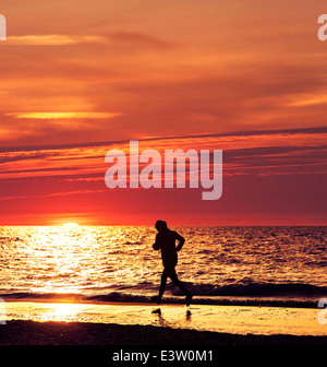Woman running at beautiful sunset in the beach. - Stock Photo
