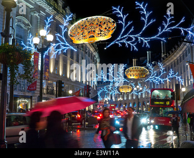 Busy scene of Christmas shoppers, traffic and umbrellas in a rain swept Regent Street with Christmas lights behind - Stock Photo