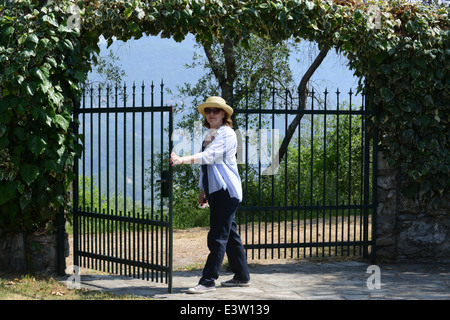 Woman opening garden home property security gate gates - Stock Photo
