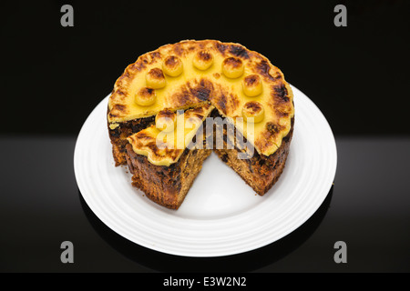 Traditional home baked round Easter simnel cake, topped with marzipan, sliced, on a circular white plate with black - Stock Photo