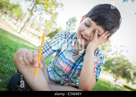Frustrated Cute Young Boy Holding Pencil Sitting on the Grass Outdoors. - Stock Photo
