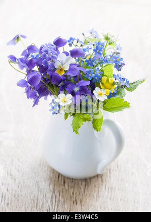 Bouquet of wild flowers in white vase on wood background, studio shot - Stock Photo
