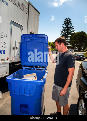 A recycling company employee piles boxed documents in a plastic container prior to destroying them using a truck - Stock Photo