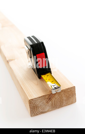 Metal imperial metric tape measure measuring two by four lumber on white background - Stock Photo