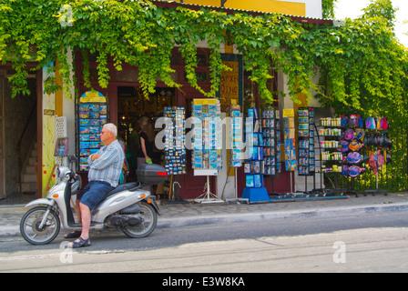Local man on scooter outside souvenir shop, Logotheti street, Pythagoreio, Samos, Greece, Europe - Stock Photo