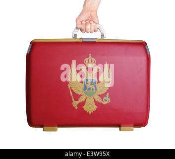 Used plastic suitcase with stains and scratches, printed with flag, Montenegro - Stock Photo