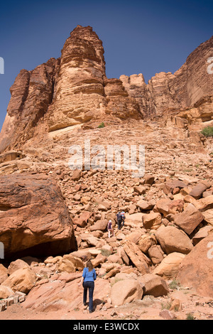 Jordan, Wadi Rum, western tourists climbing of eroded rocky desert cliffs to see fresh water spring - Stock Photo