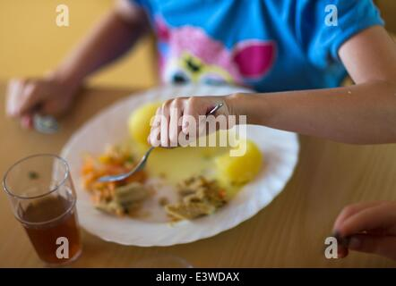 Wismar, Germany. 19th June, 2014. Nursery child Romina eats her lunch from her plate with a knife and fork at the - Stock Photo
