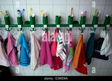 Wismar, Germany. 19th June, 2014. Colourful towels and toothbrush tumblers stand on a shelf in the washing room - Stock Photo