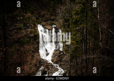 Out of the dark - waterfall in the mountains - Stock Photo