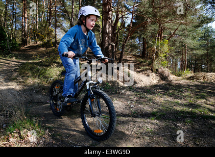 A young boy wearing a helmet rides his BMX bicycle in woodland in Hampshire, England - Stock Photo