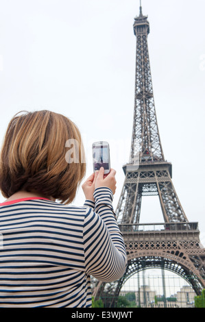 woman taking photographs of eiffel tower paris using a cellphone - Stock Photo