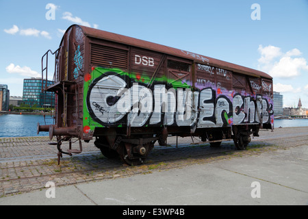 Old, colourful graffiti painted goods waggon parked at the old railway tracks on Islands Brygge, Copenhagen, Denmark. - Stock Photo