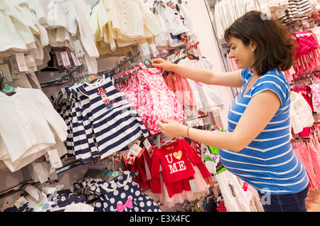 Pregnant woman buying baby clothes at Primark, England, UK - Stock Photo