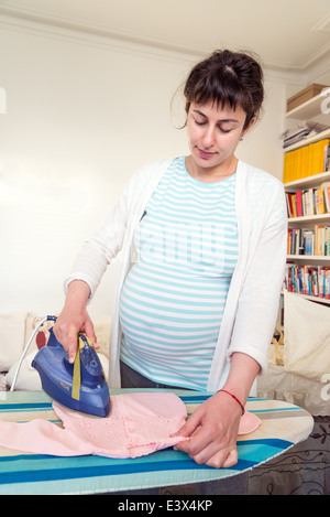 Pregnant woman ironing baby clothes in preparation for baby's arrival, England, UK - Stock Photo