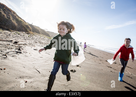 Girls picking up trash on beach cleanup day. - Stock Photo