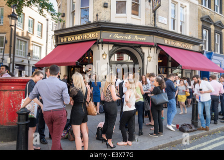 People drinking outside The Round House pub in Garrick Street, Covent Garden, London, England, UK - Stock Photo