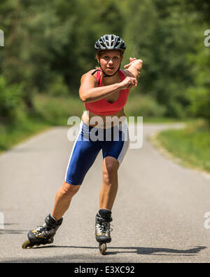 Young woman, 19 years, in-line skating, country road, Schurwald, Baden-Württemberg, Germany - Stock Photo