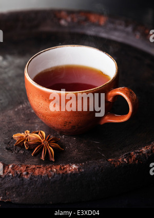 Hot tea with spices on dark background - Stock Photo