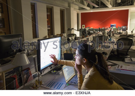 Mixed race businesswoman working late in office - Stock Photo