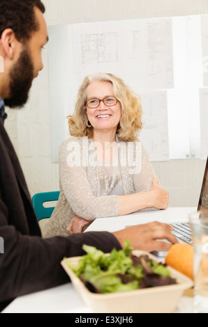 Business people having lunch together in office - Stock Photo