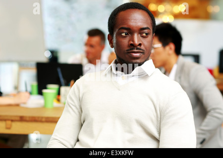 Portrait of a pensive african man looking away in office - Stock Photo