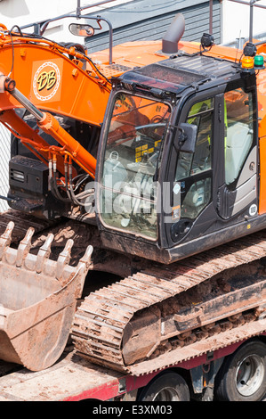 Looking down onto an excavator loaded onto the back of a low loader - Stock Photo