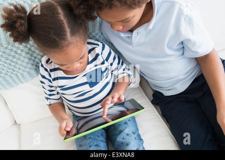 Black children using digital tablet together - Stock Photo