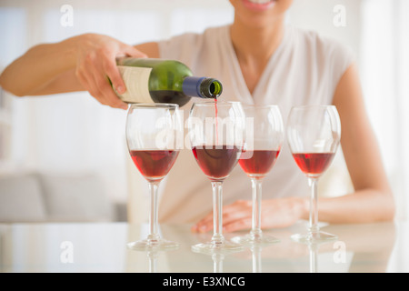 Black woman pouring glasses of wine Stock Photo