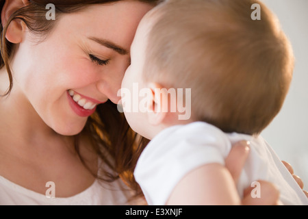 Smiling mother cradling baby - Stock Photo