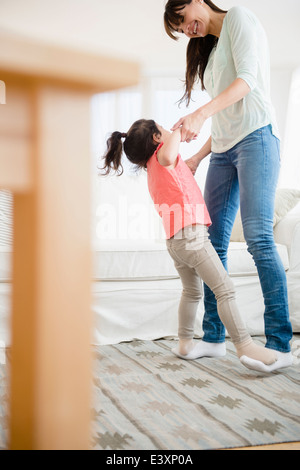 Hispanic mother and daughter dancing together - Stock Photo