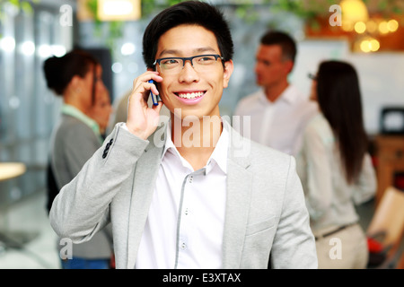 Happy asian businessman talking on the smartphone in front of colleagues - Stock Photo