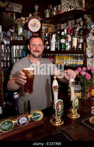UK England, Suffolk, Bury St Edmunds, holding pint of IPA in Nutshell, Britain's smallest pub - Stock Photo