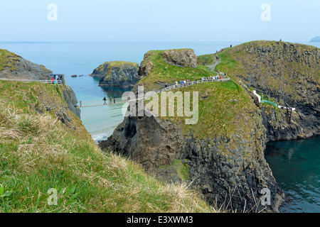 View on Carrick-a-Rede island and the famous Carrick-a-Rede rope bridge near Ballintoy in County Antrim, Northern - Stock Photo
