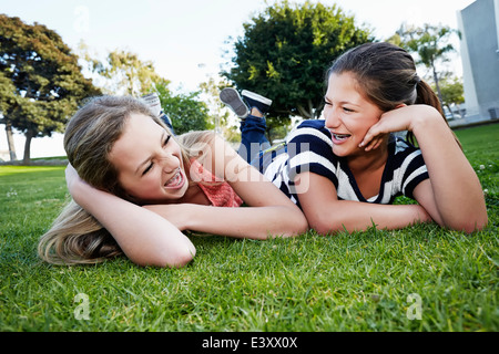 Teenage girls laying in grass