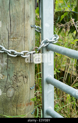 Combination padlock and chain on galvanized steel metal gate and post - Stock Photo