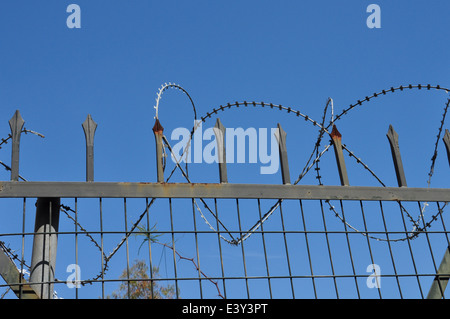 Razor barbed wire and chain link fence with rusty palisade sharp spikes. Property security abstract background. - Stock Photo