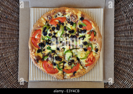Vegetarian pizza with tomato, olives, pepper, mushrooms and onions packaged in cardboard box. Italian takeaway food - Stock Photo