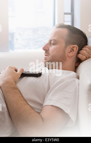 Mature man with remote control asleep on sofa