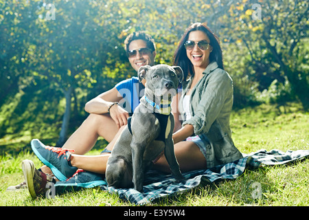 Portrait of couple and dog sitting on picnic blanket in park - Stock Photo